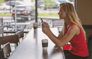 a woman in a cafe sending a text message to her ex boyfriend